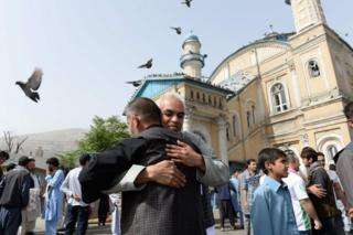 Afghan Muslims hug each other after offering prayers at the start of the Eid al-Fitr holiday which marks the end of Ramadan at the Shah-e Do Shamshira mosque in Kabul on June 15, 2018