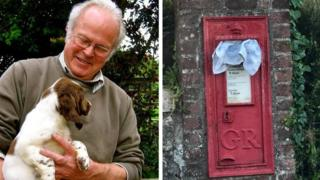 Rodney Harris with his dog/postbox with towel in letter box
