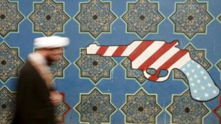 An Iranian cleric walks past a mural on the wall of the former US embassy in Tehran (11 February 2007)