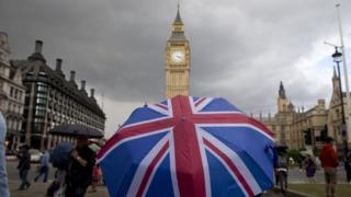 A pedestrian shelters from the rain beneath a Union flag umbrella as they walk near Big Ben