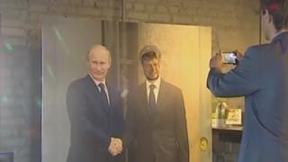A visitor poses alongside a photo of Putin