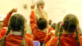 Primary school pupils putting their hands up during a lesson