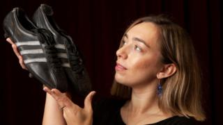 Hannah Murphy holds Tommy Gemmell's football boots