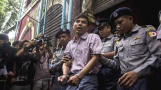 Kyaw Soe Oo (C) is escorted by police out of a court in Yangon on August 27, 2018