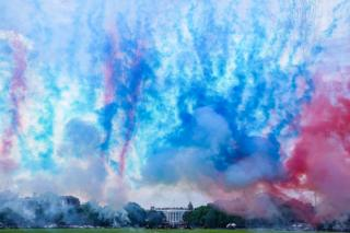 Trails of coloured smoke are seen in the air in front of the White House