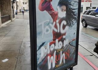 in_pictures A Mulan film poster defaced with graffiti - a mask is painted over her face, along with the words