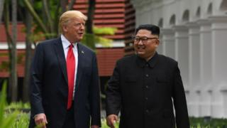 North Korea's leader Kim Jong Un (R) walks with US President Donald Trump (L) during a break in talks at their historic US-North Korea summit