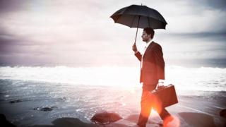 Un hombre ejecutivo que camina solo por una playa, con un paraguas en la mano