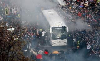 Real Madrid's supporters cheer during the arrival of the team bus next to Santiago Bernabeu stadium