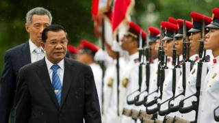 "Cambodia""s Prime Minister Hun Sen (front) inspects an honour guard as Singapore""s Prime Minister Lee Hsien Loong walks behind him at the Istana in Singapore July 26, 2010"