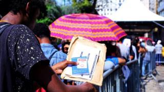 Jovem na fila do mutirão do emprego em São Paulo