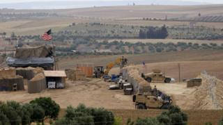 Image shows vehicles and structures of the US-backed coalition forces in the northern Syrian town of Manbij