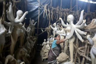 A woman paints sculptures of goddesses