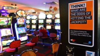"A room with poker machines, or slot machines, behind a warning poster saying: ""Think! What are the odds of hitting the jackpot?"""