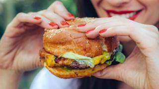 Mulher comendo hamburguer