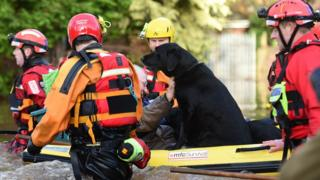 The emergency services have helped rescue people and their pets using rubber dinghies to keep them dry.