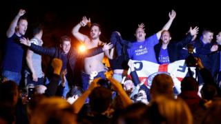 Leicester City fans celebrate their team winning the English Premier League outside the home of player Jamie Vardy