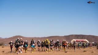 The start of the Marathon des Sables with a helicopter hanging overhead
