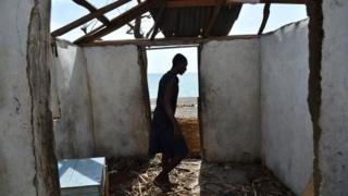 A man stands in his ruined house in Haiti after Hurricane Matthew