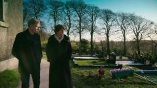 Patrick Kielty and Arlene Foster in a graveyard