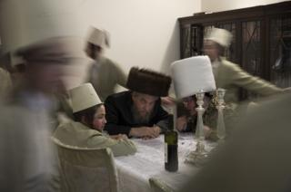 Young Jewish men dance around a table as they visit a local business man to ask for money during the annual Jewish holiday of Purim on 12 March 2017 in London, England.