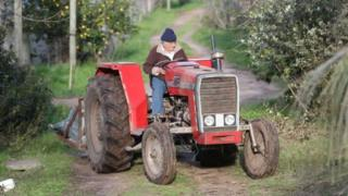 Former Uruguayan President José Mujica drives a tractor on his farm on the outskirts of Montevideo, Uruguay
