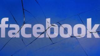 A Facebook logo displayed on a broken mobile phone screen