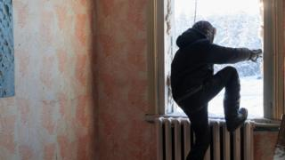 Ayal comes out through the broken window of an abandoned building after exploring it. It used to belong to an insurance company. Today, Verkhoyansk 1,131 inhabitants live in the village against twice that number 15 years ago.