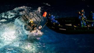 Embarcação de apoio a mergulho (DSV, na sigla em inglês) se prepara para expedição no mar, acompanhada por diversos membros da equipe