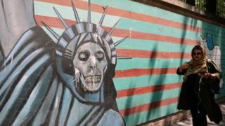 إيرانية تمر بجوار جدارية مناوئة للولايات المتحدة في طهران