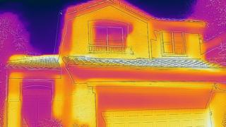 Thermal imaging camera showing heat loss from a house