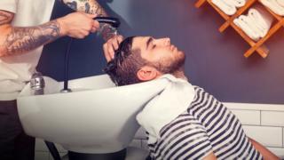 Hombre lavándose el pelo en la peluquería