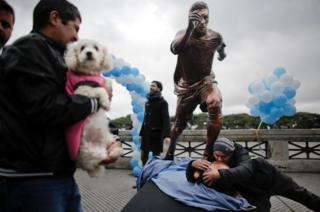 A man kisses a statue of soccer star Lionel Messi shortly after it was unveiled in Buenos Aires, Argentina