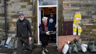People begin the clean-up following yesterday's flooding in Newcastleton, Scotland.