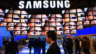 A Samsung logo appears above television screens at an electronics trade fair