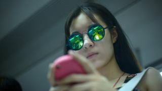 young woman in sunglasses checking her mobile