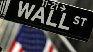 Sign for Wall Street with US flag in background
