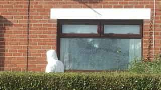 A forensic expert beside a windows damaged by shots