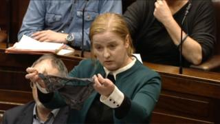 Ruth Coppinger, wearing a blazer, holds out a dark pair of underwear while standing in the dark wooden rows of seating the Irish parliament, Dáil Éireann.