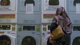 Woman standing in a laundrette