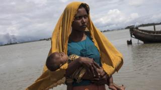 শিশু কোলে পালিয়ে আসা এক রোহিঙ্গা নারী