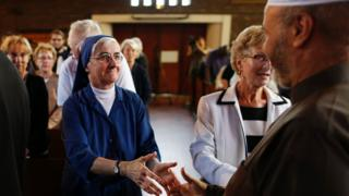 Nun shakes hands with a Muslim in Sainte-Therese church during a mass in tribute to priest Jacques Hamel on July 30, 2016 in Saint-Etienne-du-Rouvray