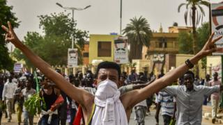 A Sudanese protester covering his face with a jersey flashes the victory gesture while marching with others in a mass demonstration against the country's ruling generals in the capital Khartoum's twin city of Omdurman on June 30, 2019.