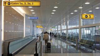 A traveller walks through the departure lounge in Terminal 3