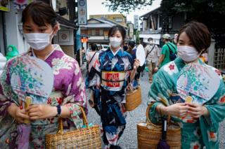 in_pictures Women wearing protective face masks walk near Kiyomizudera temple in Kyoto, Japan.