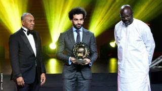 Mohamed Salah yahawe ako gashimwe na prezida wa CAF Ahmad Ahmad (i bubamfu) na prezida wa Liberia George Weah (i buryo)