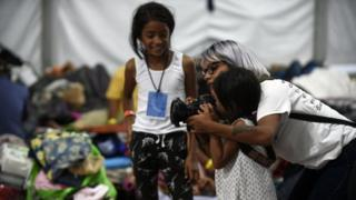 A photographer shows a young migrant girl how to use her camera