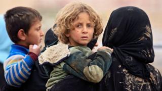 سيدة عراقية تحمل أطفالها