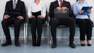 Cuatro personas esperando por una entrevista de trabajo