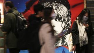 People wearing masks outside Les Miserables in London